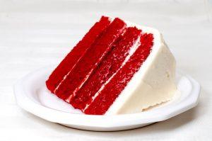 Fatia de um bolo red velvet bem tradicional com recheio e cobertura de cream cheese. sugar